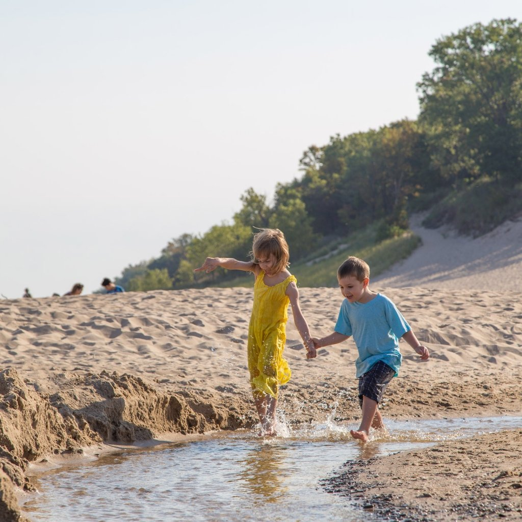 A young girl and boy are playing on the beach