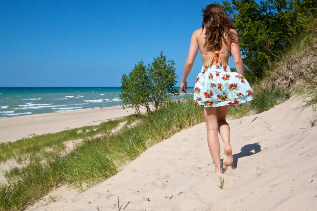 A girl walking barefoot on the beach