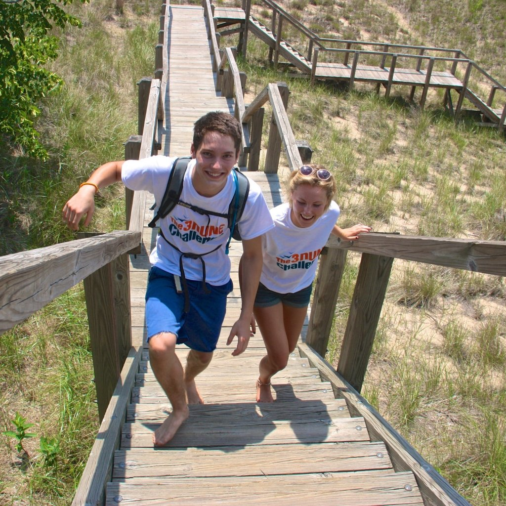 2 people walking up boardwalk stairs