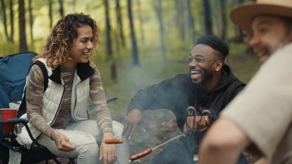 people laughing around a campfire
