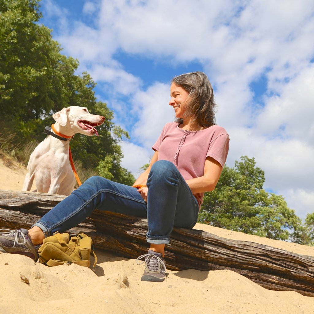 A woman and her dog sitting on the beach