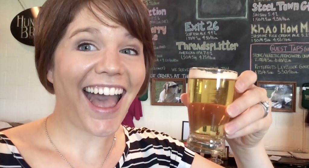 a smiling woman holds aloft a glass of beer