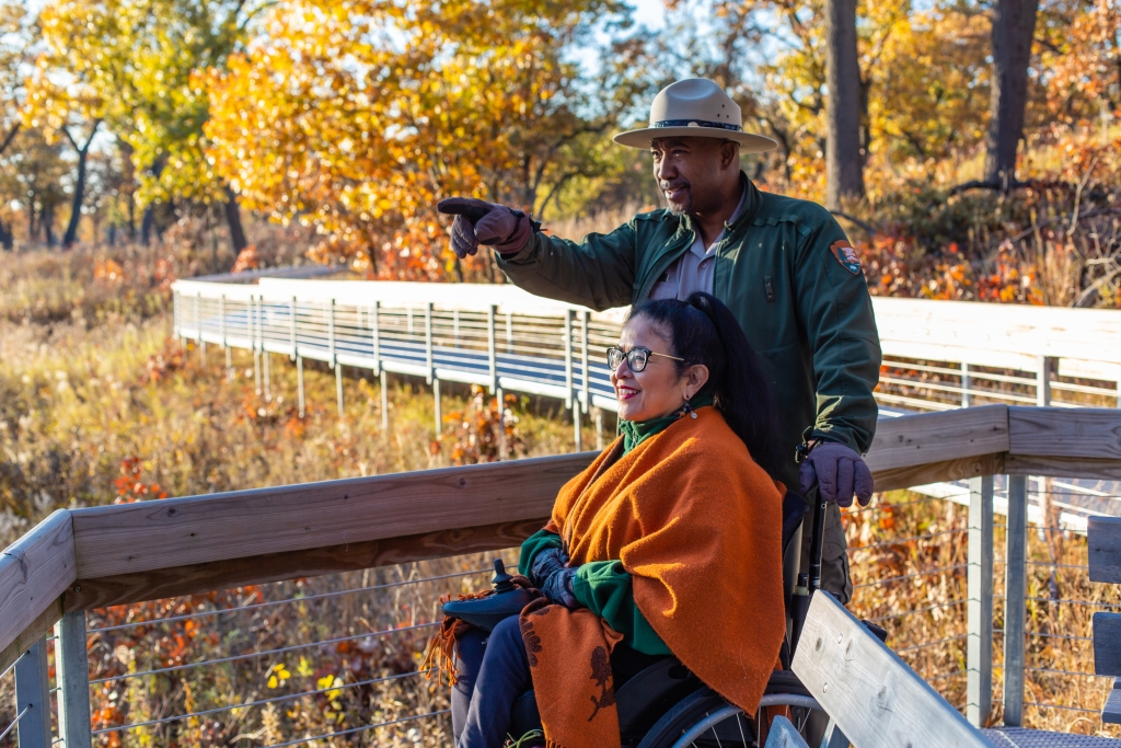 park ranger and woman view the fall colors on a boardwalk