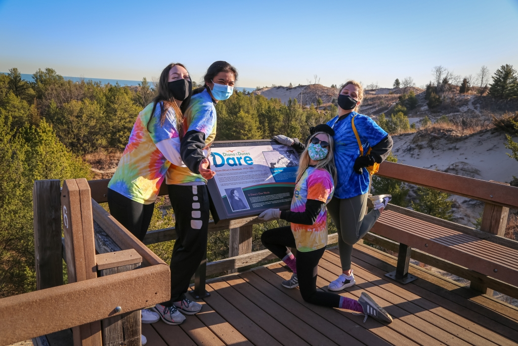 Students next to a sign on the Diana of the Dunes Trail