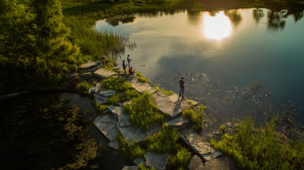 People fishing in a pond while standing on rock landscaping