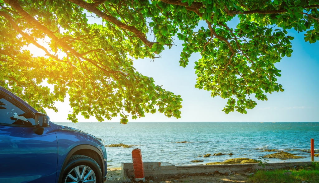 Blue sport SUV car parked by the tropical sea under umbrella tree. Summer vacation at the beach. Summer travel by car. Road trip. Automotive industry. Hybrid and electric car concept. Summer vibes.
